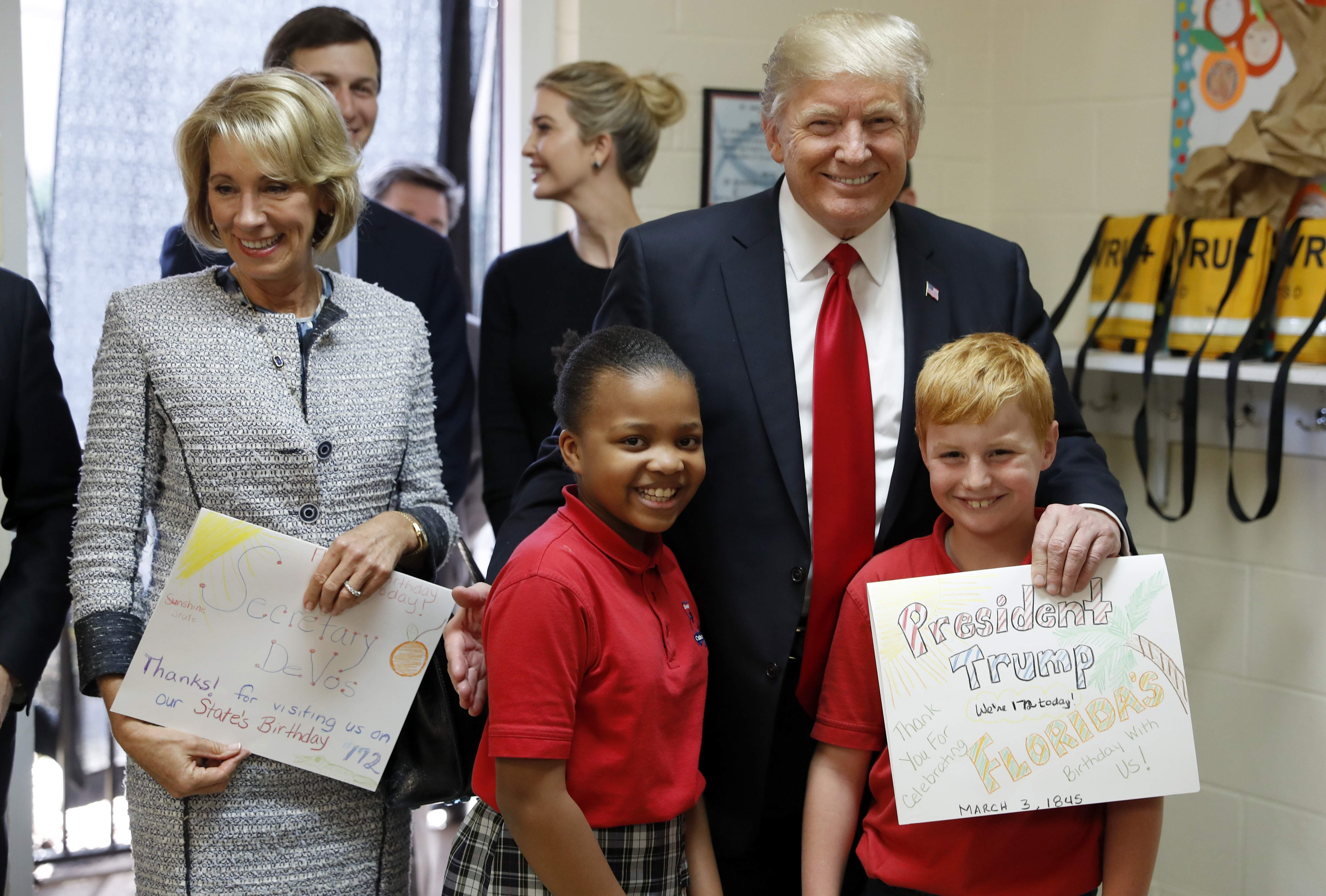 DAY 43 - In this March 3, 2017, file photo, President Donald Trump and Education Secretary Betsy DeVos pose with fourth graders Janayah Chatelier, 10, left, Landon Fritz, 10, after they received cards from the children, during a tour of Saint Andrew Catholic School in Orlando, Fla. (AP Photo/Alex Brandon, file)