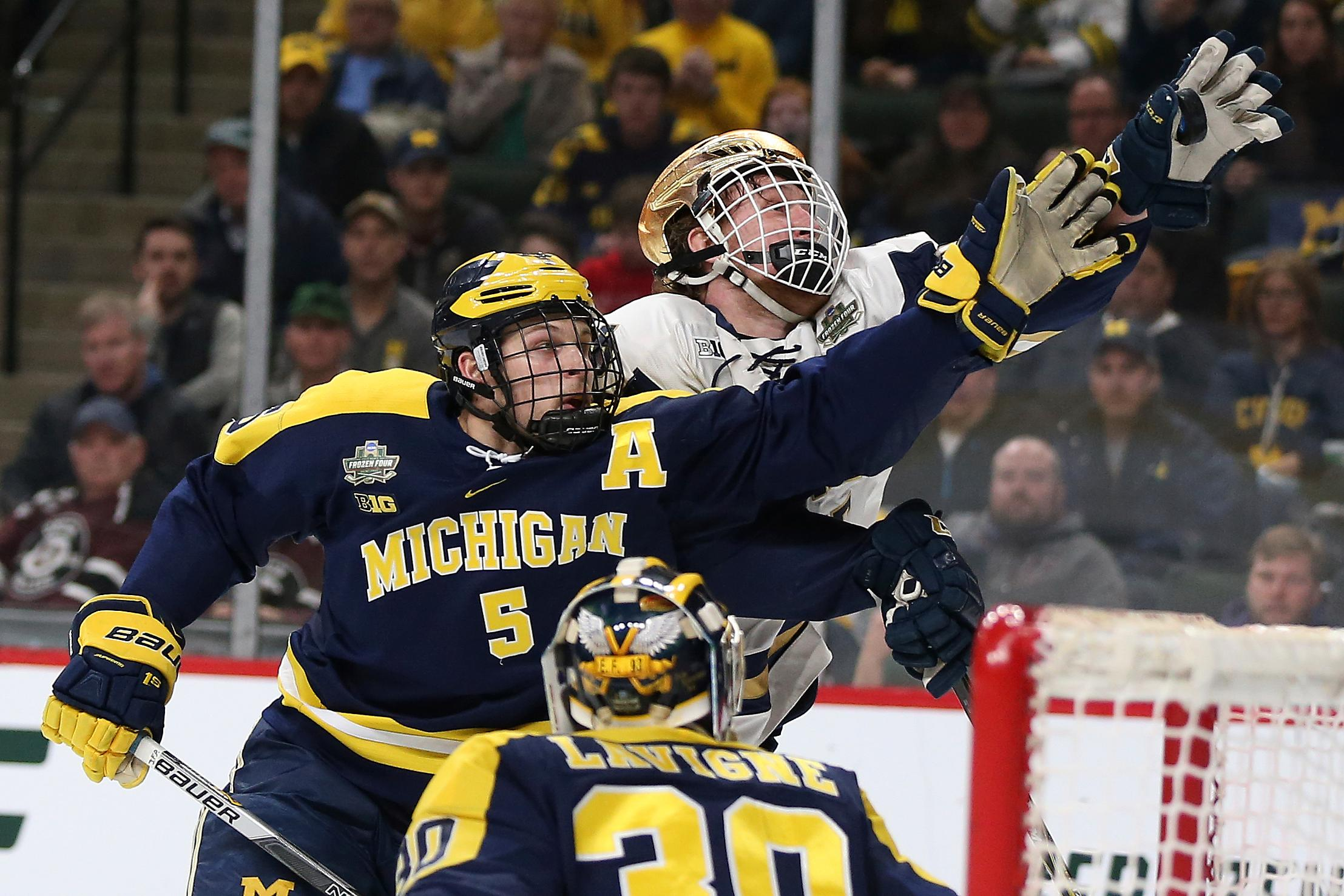 Notre Dame's Cam Morrison, right, grabs the puck out of the air next to Michigan's Griffin Luce (5) during the first period of a semifinal in the NCAA men's Frozen Four college hockey tournament Thursday, April 5, 2018, in St. Paul, Minn. (AP Photo/Stacy Bengs)