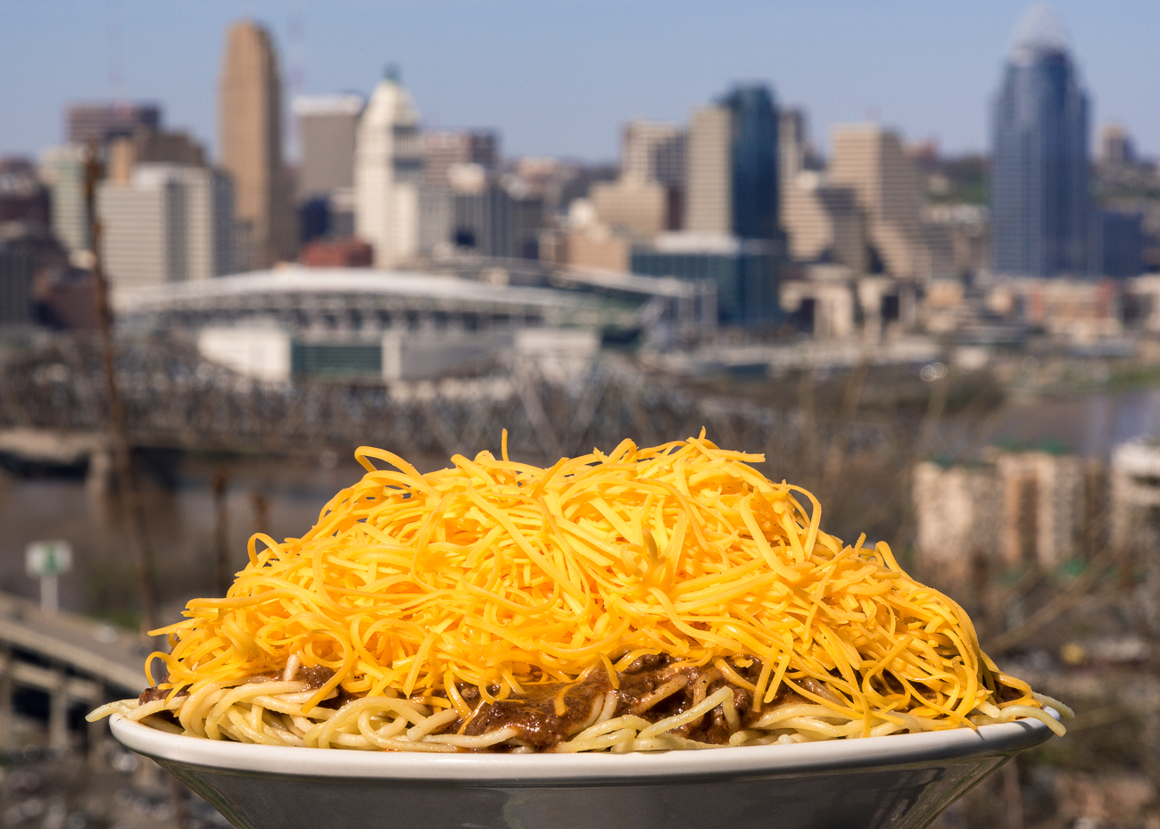 "Gold Star Chili debuted a vegetarian chili this year, so we ran around with them, taking photos of 3-ways in recognizable Cincinnati and NKY locations. Pictured is a 3-way in Devou Park with the city beyond. First published on April 25 in ""Now Vegetarians Can Enjoy Gold Star Chili Like Every Other Queen City Carnivore"" / Image: Phil Armstrong"
