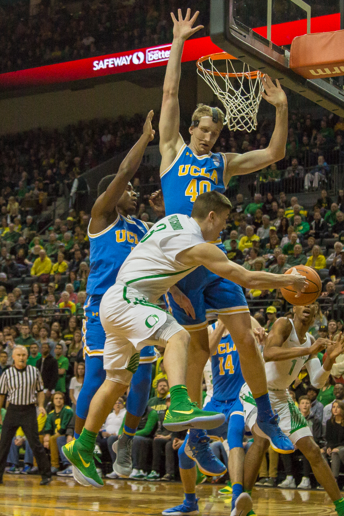 Oregon guard Payton Pritchard (#3) passes the ball around UCLA center Thomas Welsh (#40). The Oregon Ducks men's basketball team defeated the UCLA Bruins 94-91 Saturday night in front of a home crowd at Matthew Knight Arena. The win brings the Ducks 13-7 overall for the season and 3-4 in Pac-12 play. Photo by Dillon Vibes