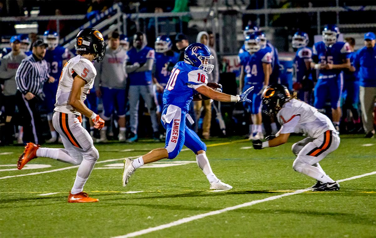 Churchill's Tyson Bennion (#10) puts yards on the Crater Comets. Churchill defeated Crater 63-21 on Friday at their homecoming game. Churchill remains undefeated with a conference record of 9-0. Photo by August Frank, Oregon News Lab