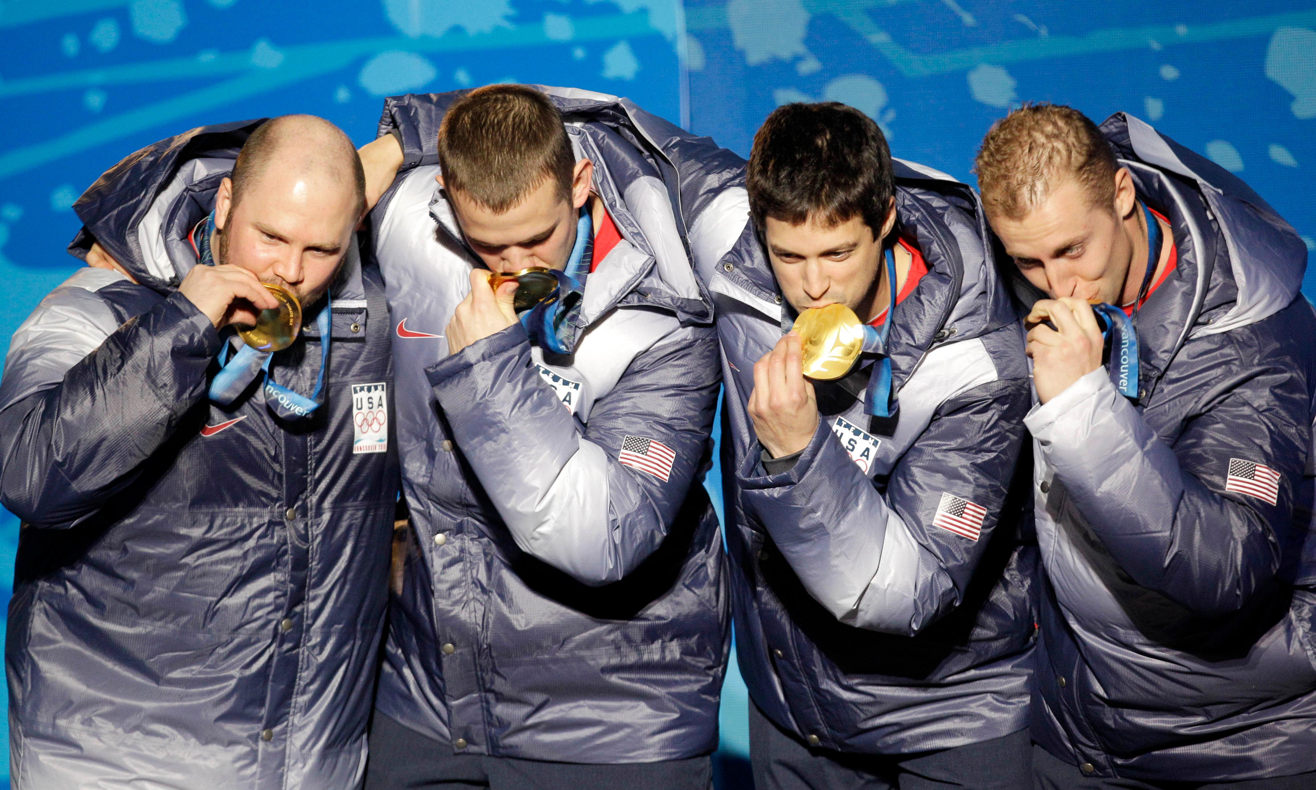 FILE - In this Feb. 27, 2010, file photo, from left, Steven Holcomb, Justin Olsen, Steve Mesler and Curtis Tomasevicz, of the United States, kiss their gold medasl in the men's four-man bobsled during the medal ceremony of the Vancouver 2010 Olympics in Whistler, British Columbia.  Holcomb, the longtime U.S. bobsledding star who drove to three Olympic medals after beating a disease that nearly robbed him of his eyesight, was found dead in Lake Placid, N.Y., on Saturday, May 6, 2017.  He was 37.(AP Photo/Jin-man Lee, File)