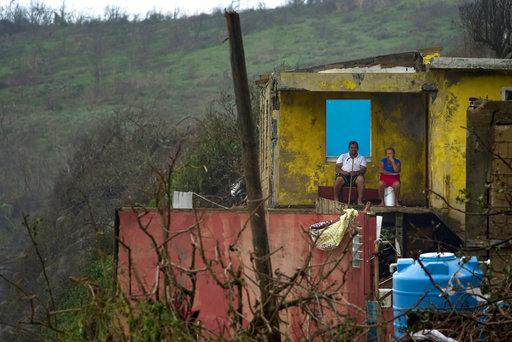 A couple is seen from the distance sitting in their home in El Negro community a day after the impact of Hurricane Maria, in Puerto Rico, Thursday, September 21, 2017. As of Thursday evening, Maria was moving off the northern coast of the Dominican Republic with winds of 120 mph (195 kph). The storm was expected to approach the Turks and Caicos Islands and the Bahamas late Thursday and early Friday. (AP Photo/Carlos Giusti)