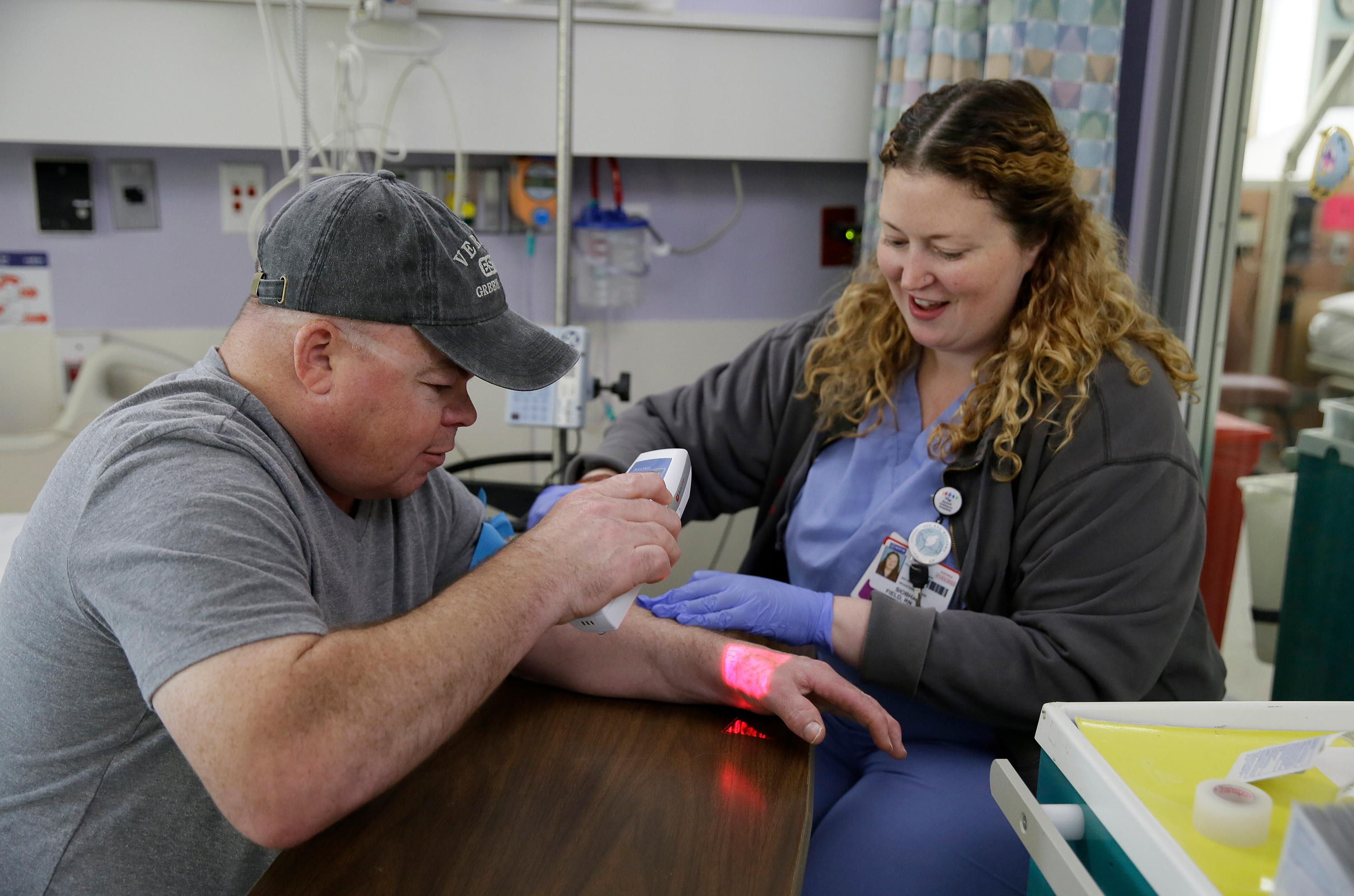 Brian Madeux, 44, uses an infrared device to look at his veins as nurse Siobhan Field prepares an IV line for the first human gene editing therapy for NPS, at the UCSF Benioff Children's Hospital Oakland in Oakland, Calif., on Monday, Nov. 6, 2017.  Madeux, who has a metabolic disease called Hunter syndrome, will receive billions of copies of a corrective gene and a genetic tool, through an IV,  to cut his DNA in a precise spot. (AP Photo/Eric Risberg)