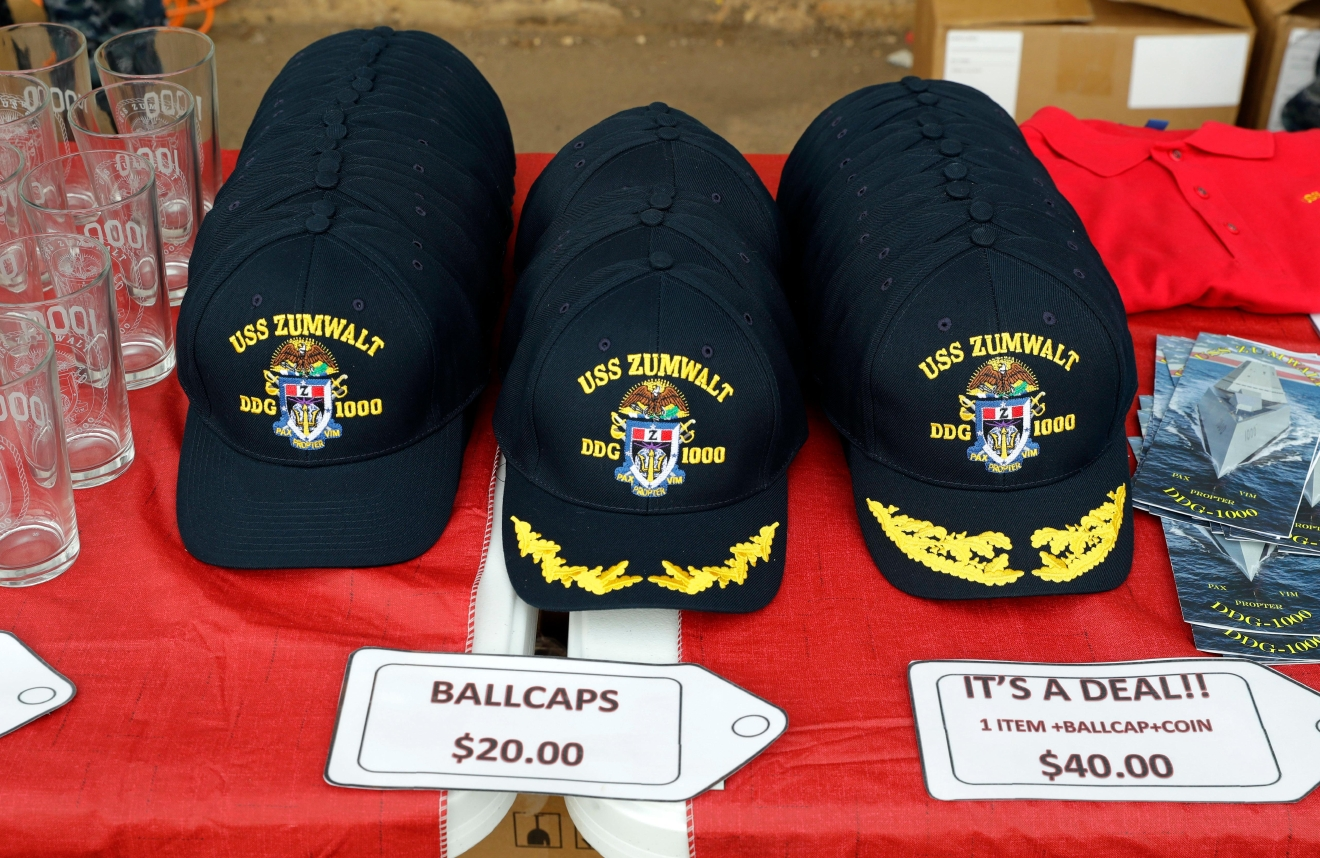This Oct. 13, 2016 photo shows hats for sale on a dock alongside the future USS Zumwalt, the U.S. Navy's newest guided-missile destroyer, in Baltimore.   The destroyer's commissioning ceremony is set for Oct. 15 in Baltimore, and its home port will be in San Diego. (AP Photo/Patrick Semansky)