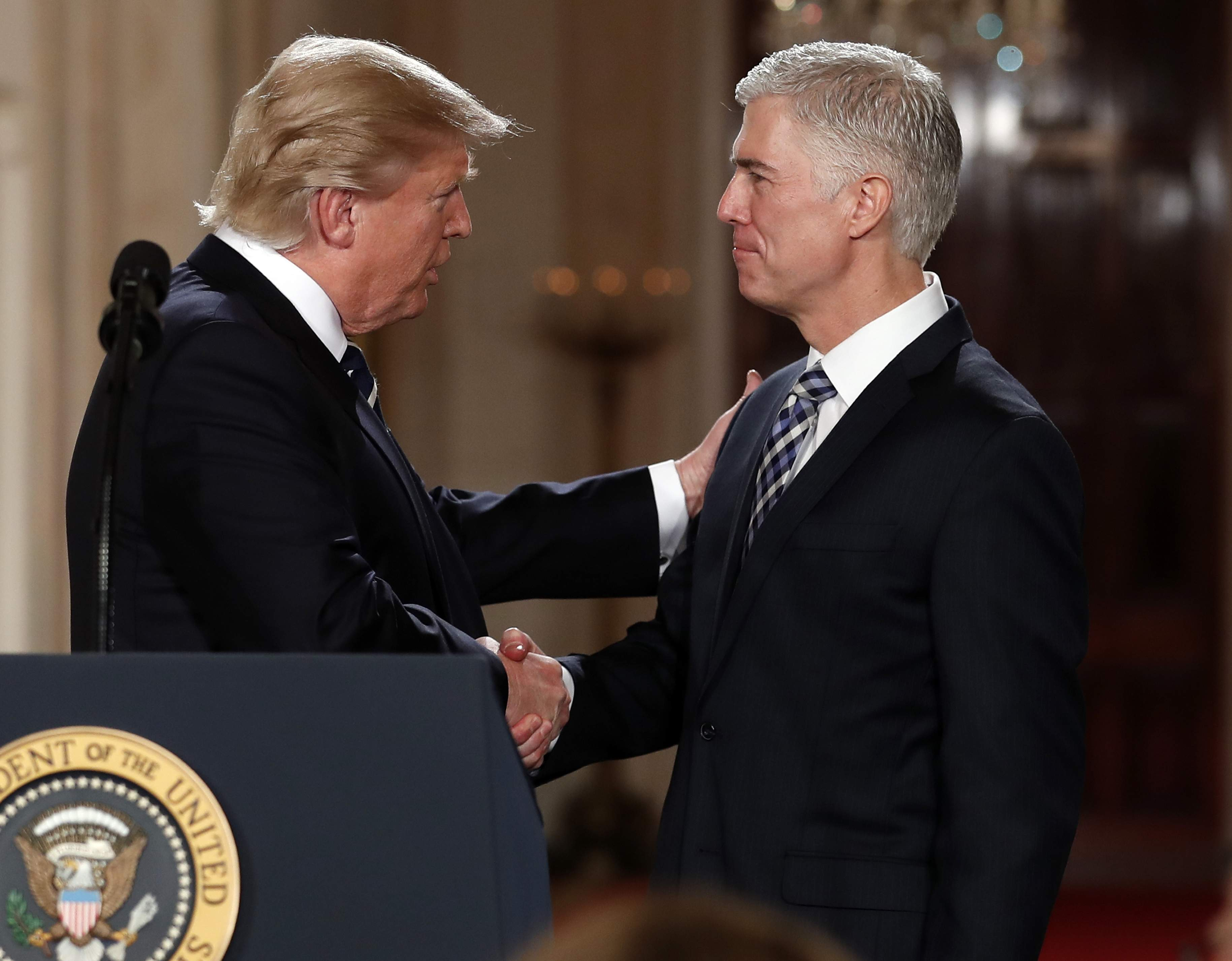 DAY 12 - In this Jan. 31, 2017, file photo, President Donald Trump shakes hands with 10th U.S. Circuit Court of Appeals Judge Neil Gorsuch, his choice for Supreme Court associate justice in the East Room of the White House in Washington. (AP Photo/Carolyn Kaster, File)