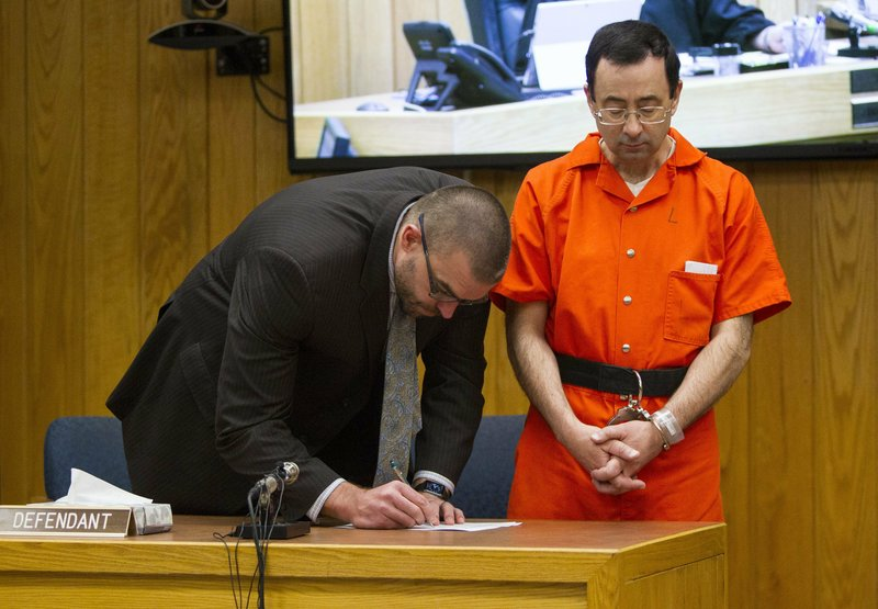 Defense attorney Matthew Newberg, left, signs court documents after Judge Janice Cunningham sentenced Larry Nassar, right, at Eaton County Circuit Court in Charlotte, Mich., Monday, Feb. 5, 2018. The former Michigan State University sports-medicine and USA Gymnastics doctor received 40 to 125 years for three first degree criminal sexual abuse charges related to assaults that occurred at Twistars, a gymnastics facility in Dimondale. Nassar has also been sentenced to 60 years in prison for three child pornography charges in federal court and between 40 to 175 years in Ingham County for seven counts of criminal sexual conduct. (Cory Morse /The Grand Rapids Press via AP)