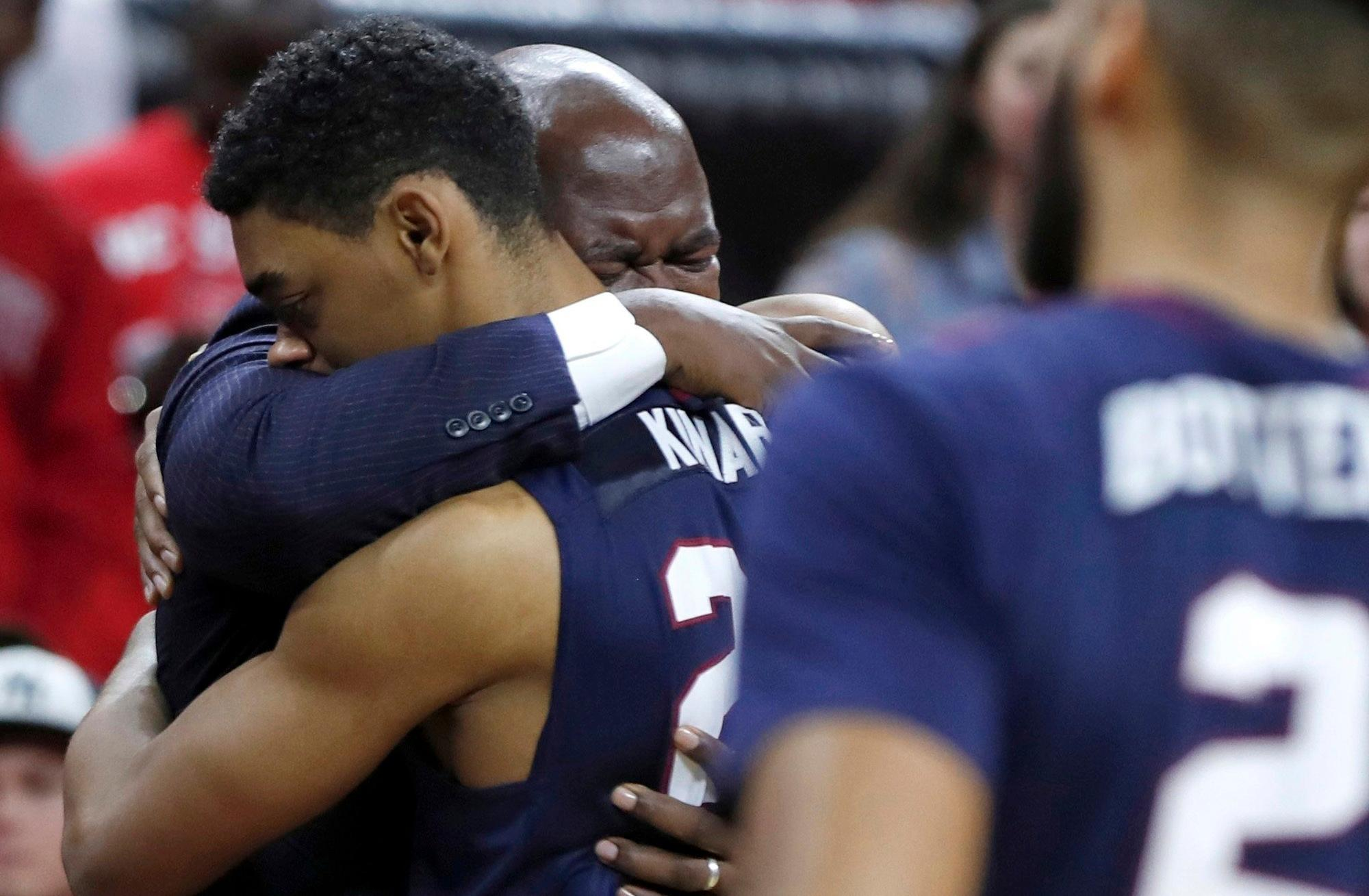 South Carolina State head coach Murray Garvin hugs Ian Kinard (24) as Tyvoris Solomon is attended to after he was injured during the first half of an NCAA college basketball game against North Carolina State at PNC Arena in Raleigh, N.C., Saturday, Dec. 2, 2017.  (Ethan Hyman/The News & Observer via AP)