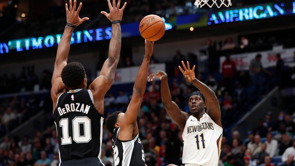 New Orleans Pelicans guard Jrue Holiday (11) passes between San Antonio  Spurs guard DeMar DeRozan (10) and forward Rudy Gay (22) in the first half  of an NBA ...