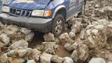 Rock wall collapses after storms, damages nearby vehicles