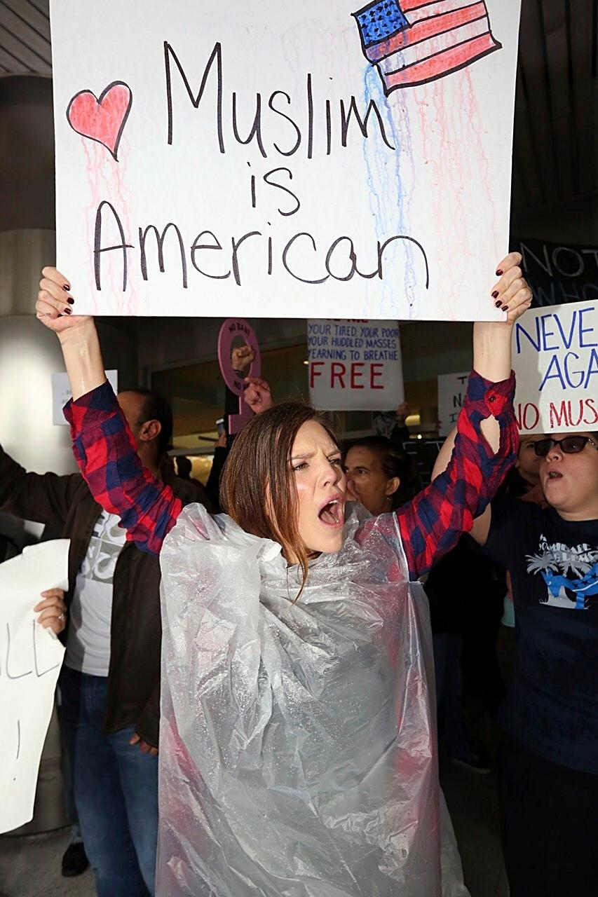 Tristan Houghton protests against President Trump's refugee ban at Miami International Airport on Sunday, Jan. 29, 2017. President Donald Trump's immigration order sowed more confusion and outrage across the country Sunday, with travelers detained at airports, panicked families searching for relatives and protesters registering their opposition to the sweeping measure. (C.M. Guerrero/El Nuevo Herald via AP)
