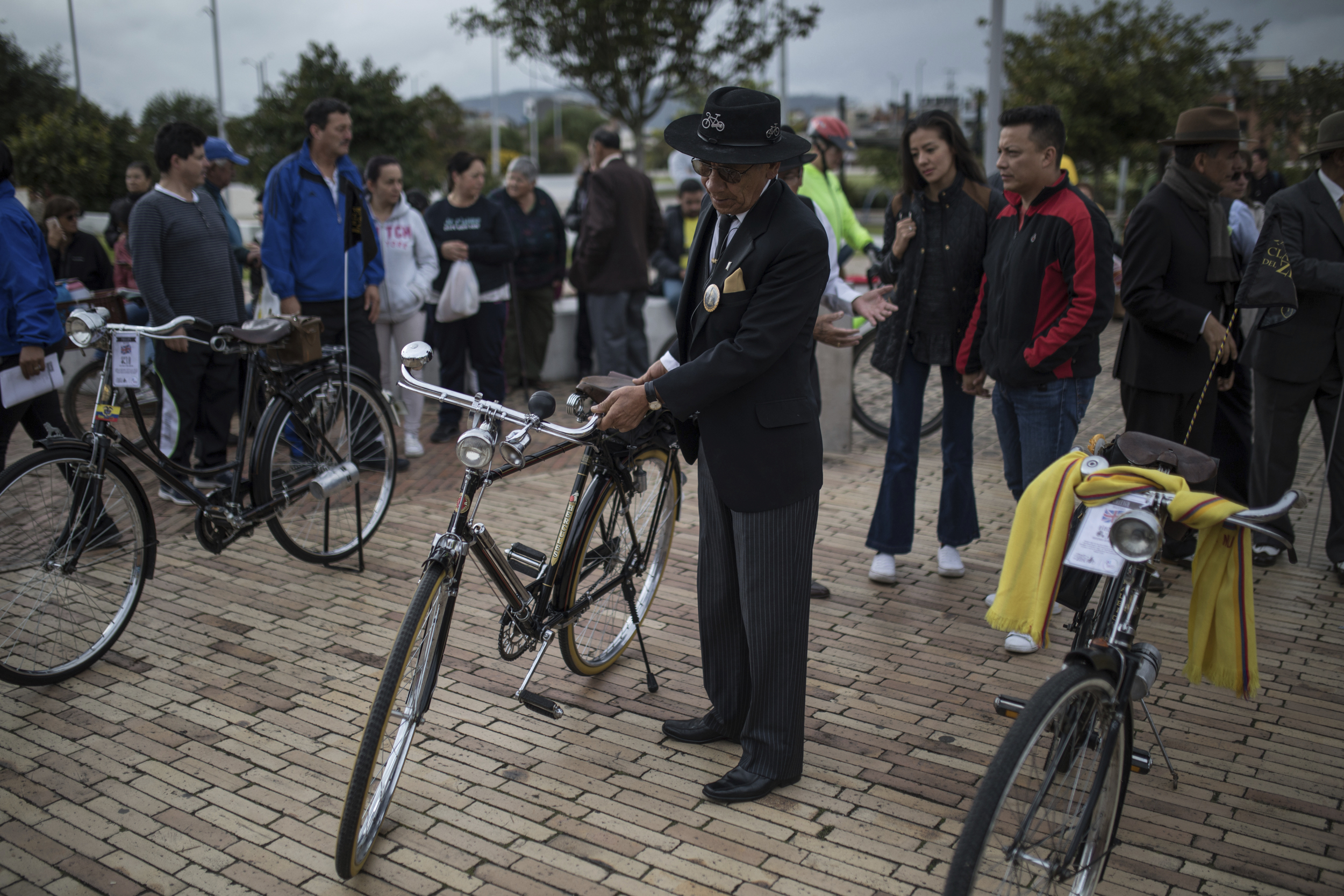 A member of the Zipaquira Old Bicycles Club parks his bike at the main square of the hometown of cyclist Egan Bernal in Zipaquira, Colombia, Sunday, July 28, 2019. Barring a crash or a last-minute health issue Bernal will become the first Colombian to win the cycling's biggest race when the Tour de France ends on Paris' Champs-Elysees on Sunday. (AP Photo/Ivan Valencia)