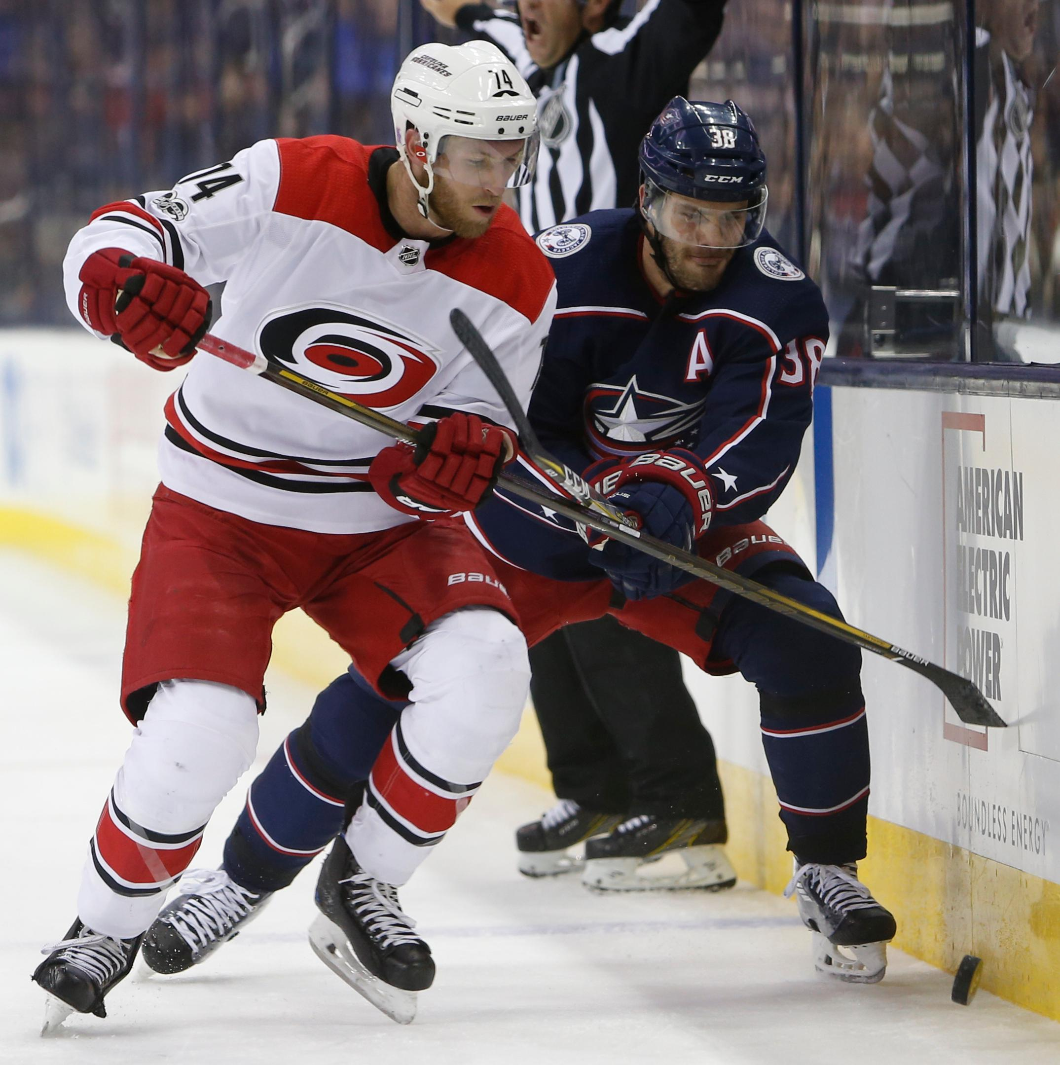 Carolina Hurricanes' Jaccob Slavin, left, and Columbus Blue Jackets' Boone Jenner scrap for a loose puck during the second period of an NHL hockey game Friday, Nov. 10, 2017, in Columbus, Ohio. (AP Photo/Jay LaPrete)