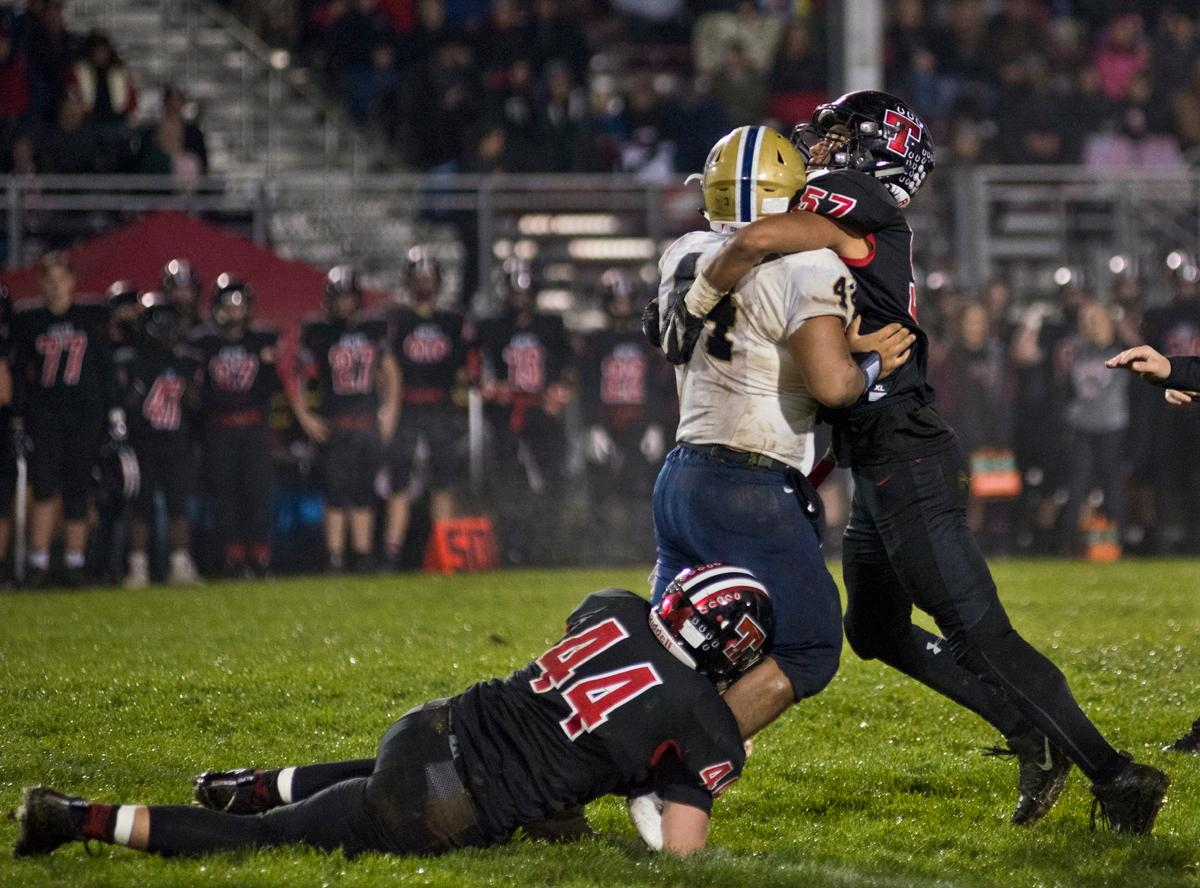 Marist Spartans running back Aavonte Clark (#44, white jersey) is stopped by Thurston Colts defensive end Akili Alvarado (#57) and linebacker Jake Riley (#44, black jersey). Thurston defeated Marist 50 to 14 to seal the second position in their conference. Photo by Dan Morrison, Oregon News Lab