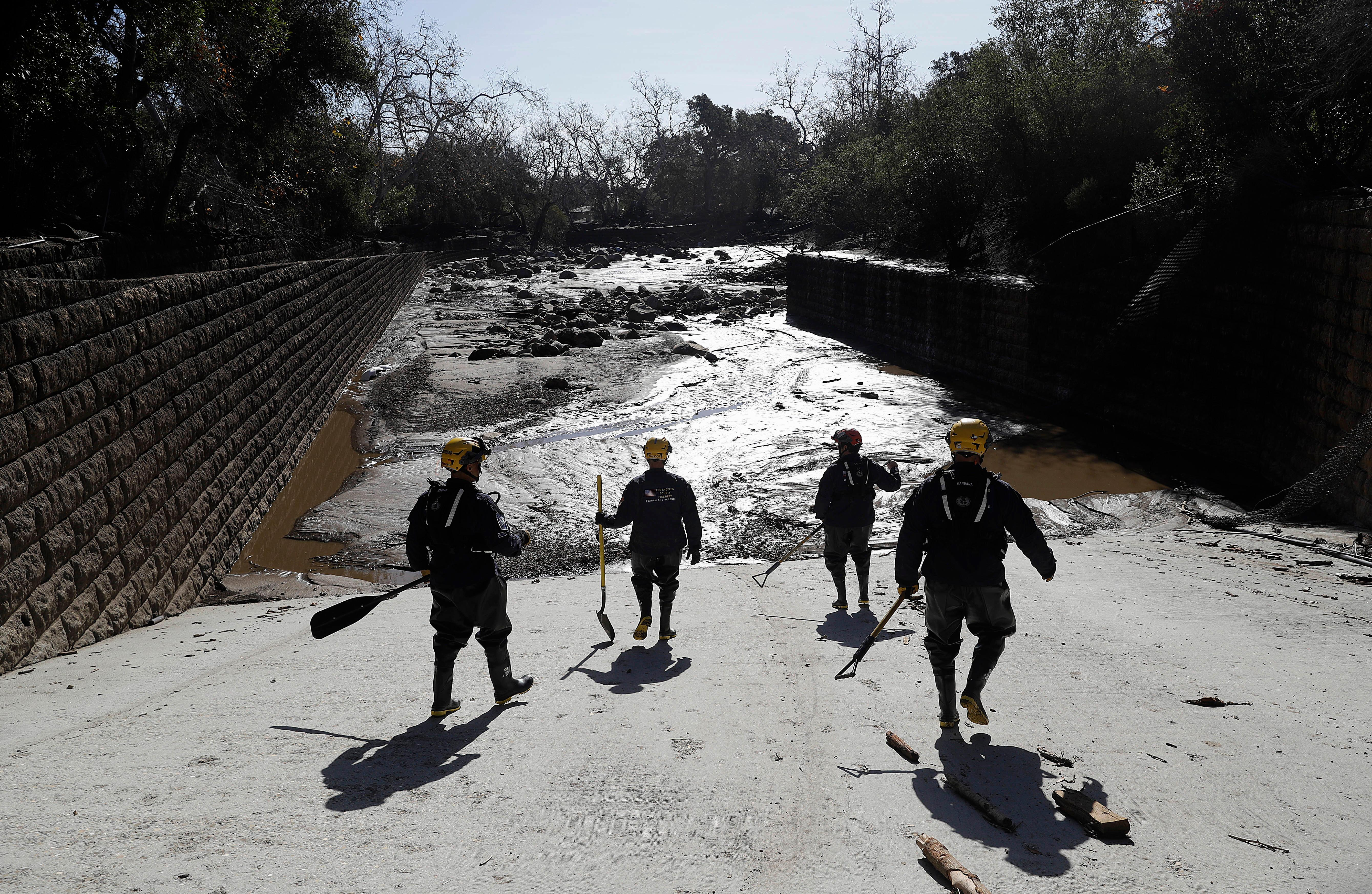 Members of the Los Angeles County Fire Department Search and Rescue crew walk toward flooded waters in Montecito, Calif., Wednesday, Jan. 10, 2018. Dozens of homes were swept away or heavily damaged and several people were killed Tuesday as downpours sent mud and boulders roaring down hills stripped of vegetation by a gigantic wildfire that raged in Southern California last month. (AP Photo/Marcio Jose Sanchez)