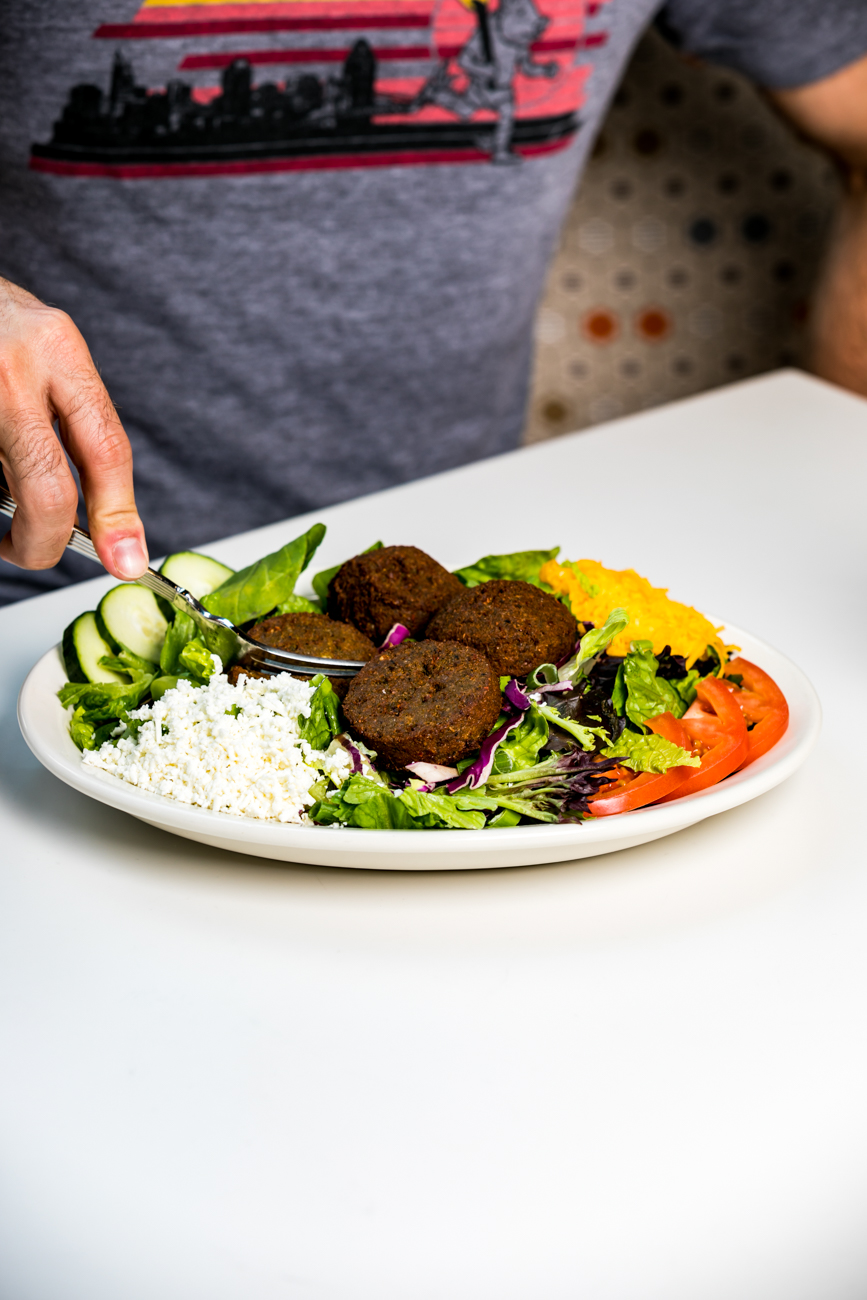 <p>Falafel Salad: Crispy falafel patties over mixed greens, sliced cucumbers, tomatoes, and scallions served with tahini yogurt dressing and your choice of cheddar or feta cheese / Image: Amy Elisabeth Spasoff // Published: 7.19.18</p>