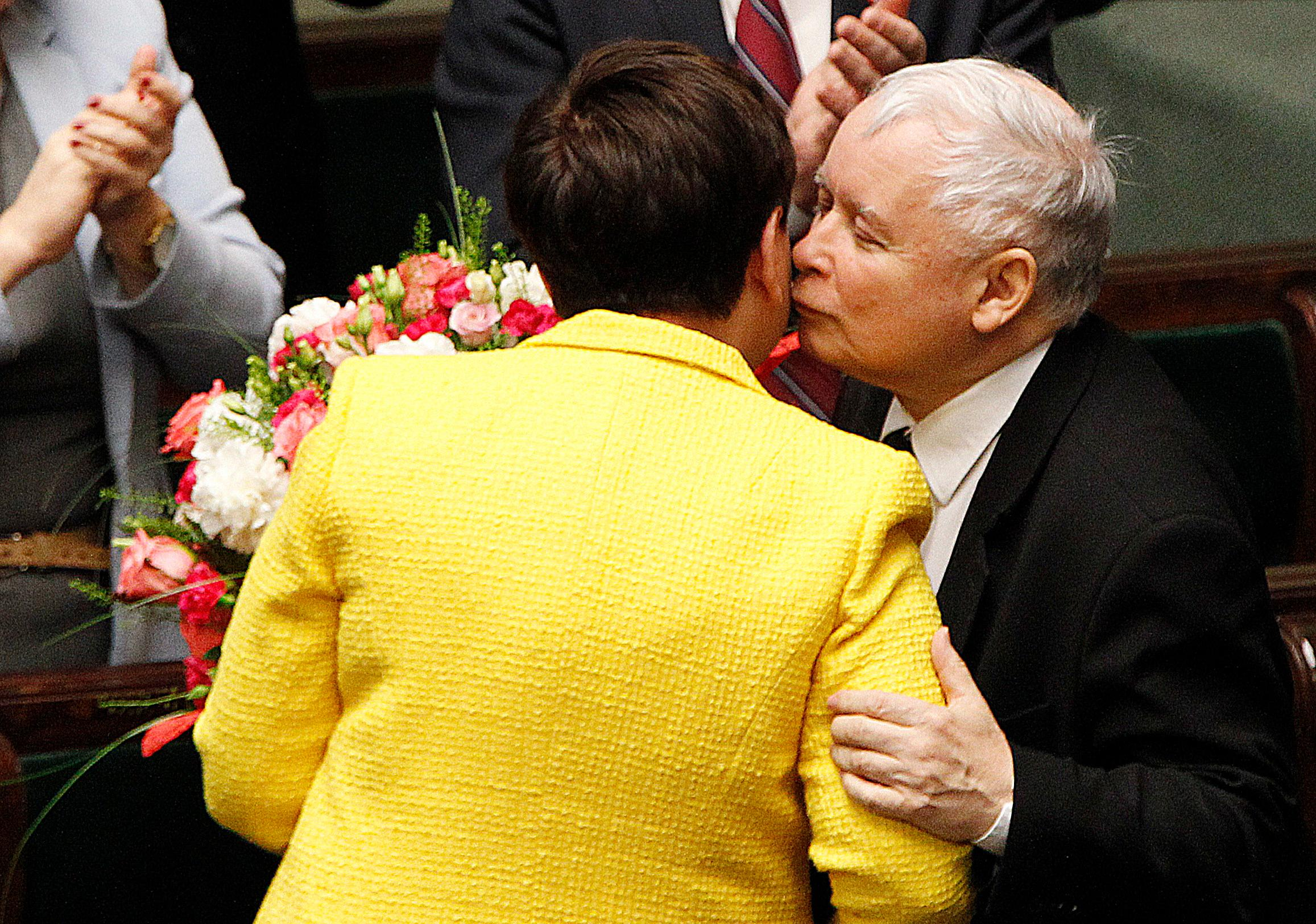 Jaroslaw Kaczynski, the powerful leader of Poland's ruling Law and Justice party gives Prime Minister Beata Szydlo a kiss and a bunch of flowers after her government survived a vote in which the opposition was seeking to oust it, at the parliament building in Warsaw, Poland, Thursday, Dec. 7, 2017. (AP Photo/Czarek Sokolowski)