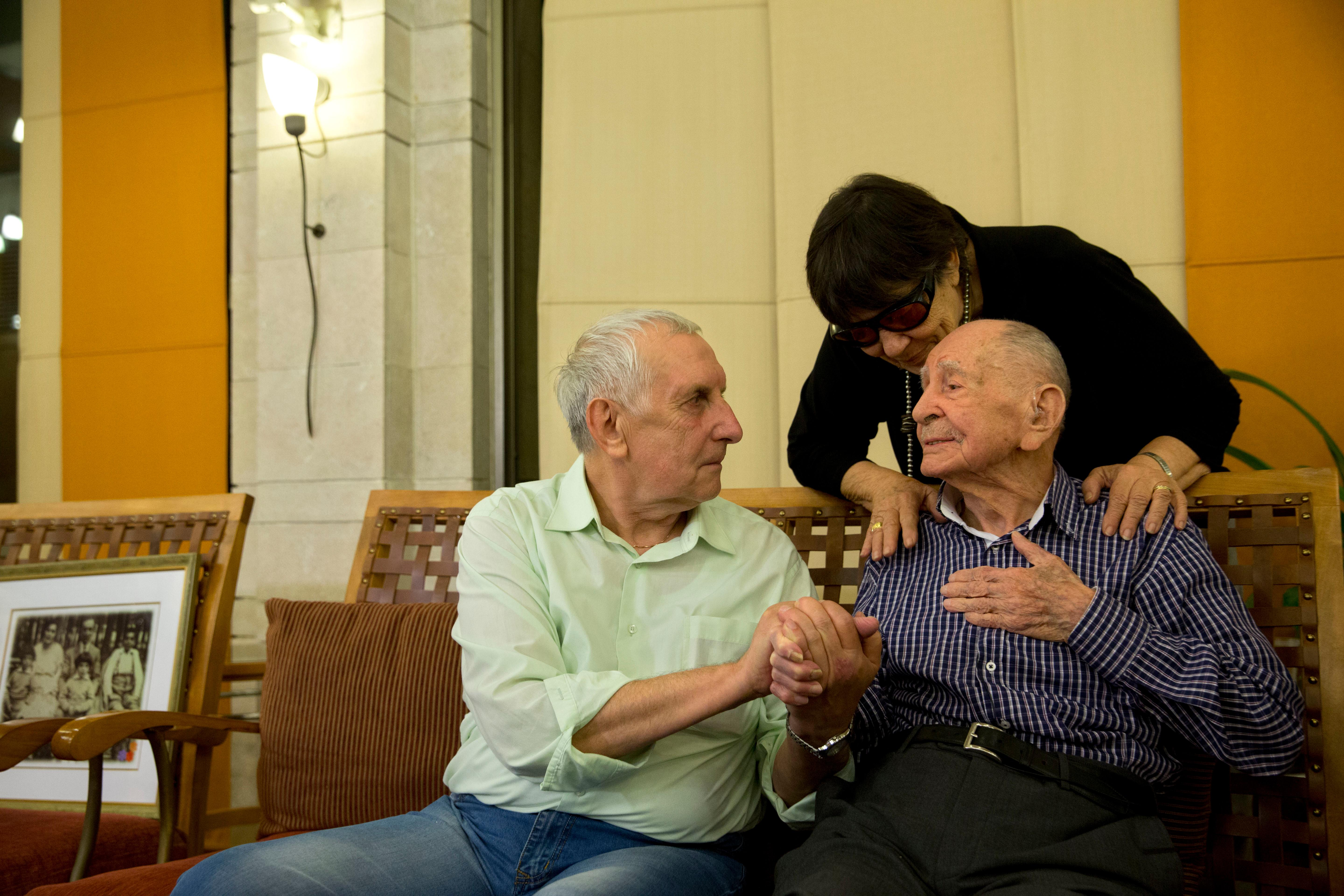In this Thursday, Nov. 16, 2017 photo, Israeli Holocaust survivor Eliahu Pietruszka, right, speaks with Alexandre Pietruszka as they meet for the first time in the central Israeli city of Kfar Saba. Pietruszka who fled Poland at the beginning of World War II and thought his entire family had perished learned that a younger brother had also survived, and his son, 66-year-old Alexandre, flew from Russia to see him. (AP Photo/Sebastian Scheiner)