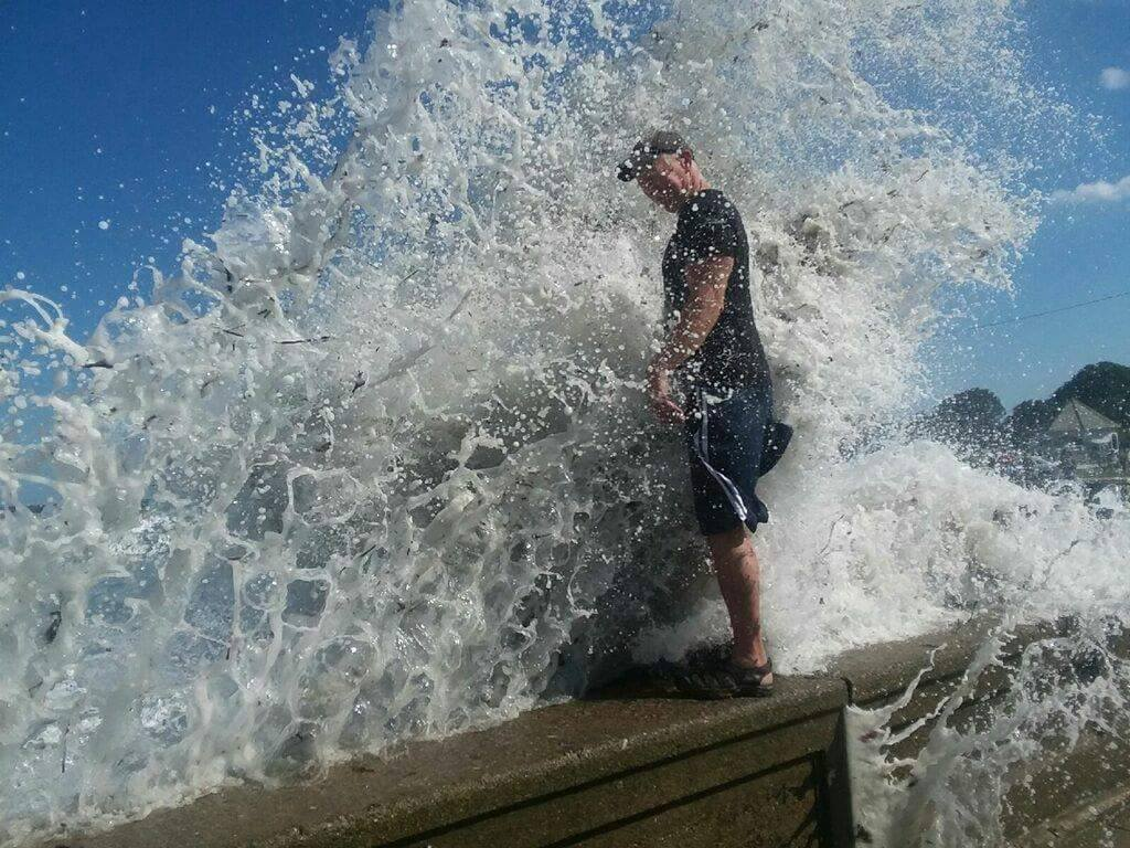 NBC 10 viewers sent in multiple photos that show the intensity of the waves. In one photo, a wave is splashing on Mike Bryce, a local artist who was standing on the seawall. (Photo courtesy of Kerri Simas)
