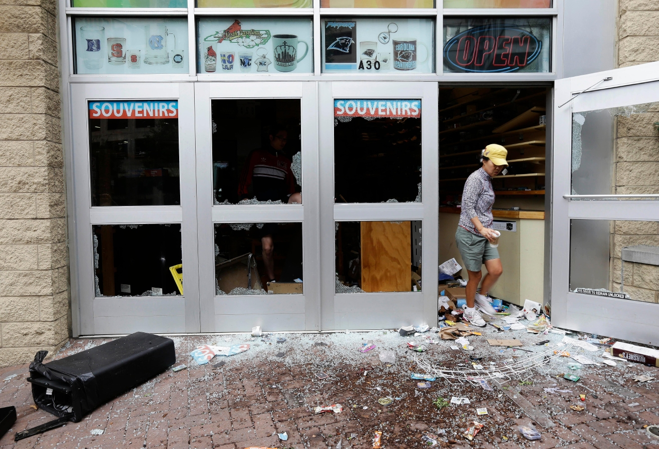 A woman emerges from a storefront following damage from overnight protests stemming from Tuesday's police shooting of Keith Lamont Scott in Charlotte, N.C., Thursday, Sept. 22, 2016. (AP Photo/Gerry Broome)
