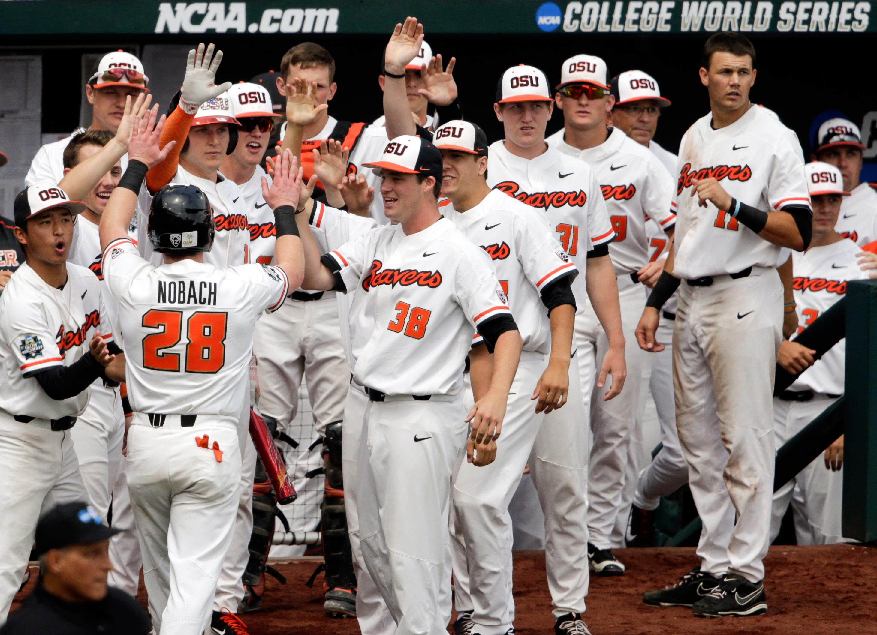 Oregon State's Kyle Nobach (28) is greeted at the dugout after he scored against Mississippi State on a one-run single by Michael Gretler in the second inning of an NCAA College World Series baseball game in Omaha, Neb., Friday, June 22, 2018. (AP Photo/Nati Harnik)